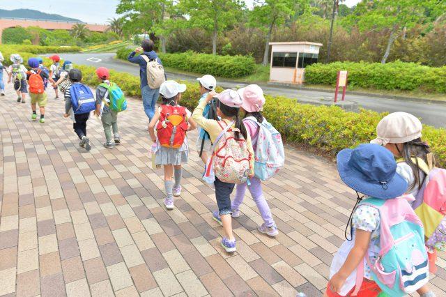 公園前の歩道を歩く園児たち