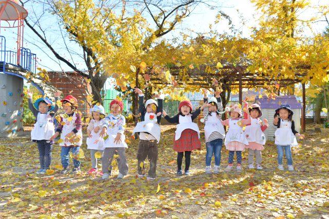 紅葉した木をバックに集まる園児たち