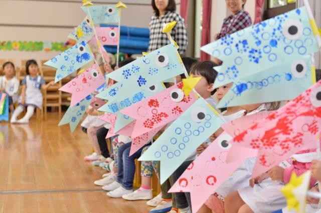 紙工作のこいのぼりを持つ園児たち